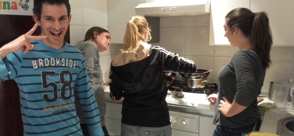 Joves cuinant en un pis adaptat a persones amb intel·ligència límit